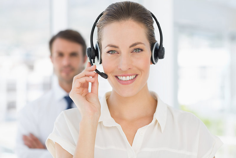 Close-up of a beautiful female executive with headset in a bright office